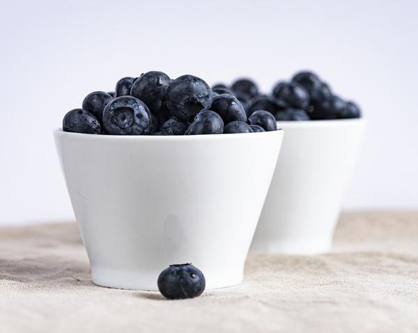 Blåbär i två vita skålar - blåbär kan motverka tarminflammationer.